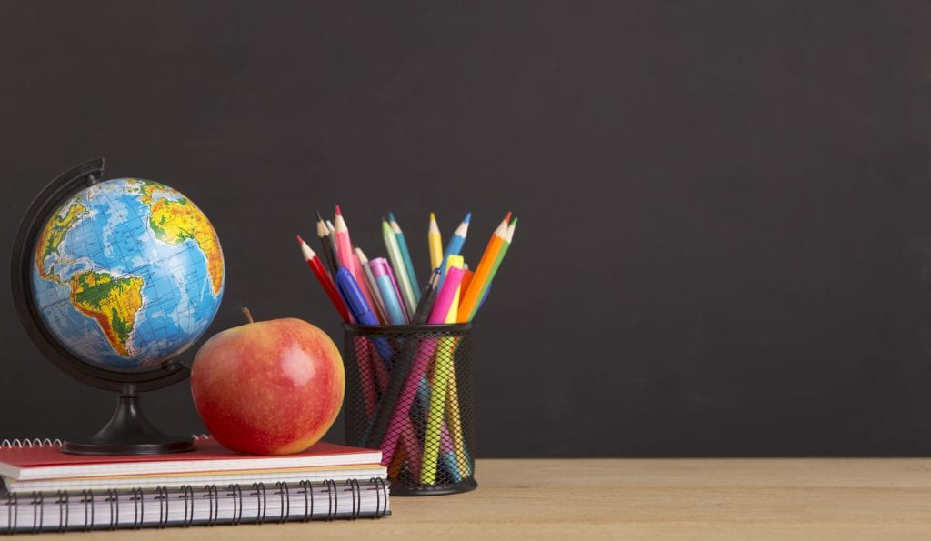 Stationery, world globe and apple over black board